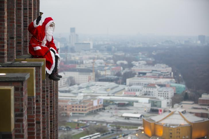 A man dressed as a Santa Claus poses at the front of the Kollhoff Tower at Potsdamer Platz square in Berlin December 14, 2014.  REUTERS/Hannibal Hanschke (GERMANY  - Tags:  SOCIETY TPX IMAGES OF THE DAY)