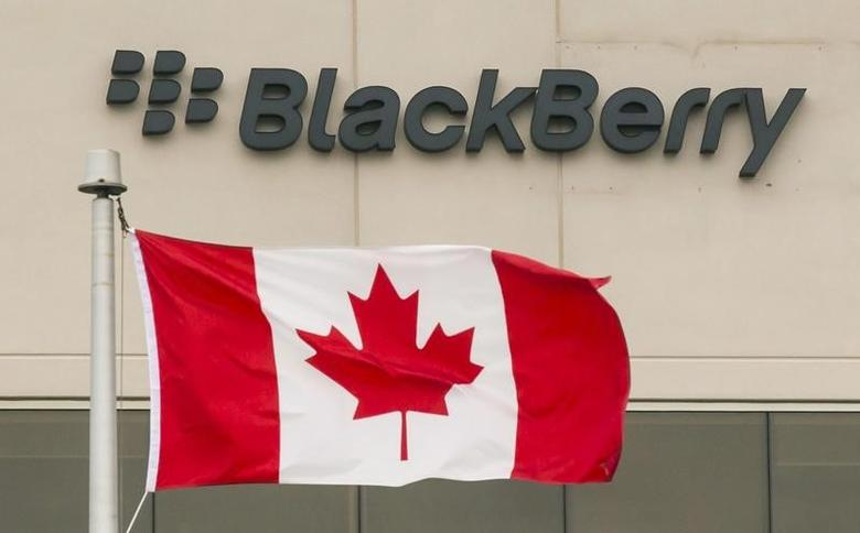 A Blackberry logo hangs behind a Canadian flag at their offices on the day of their annual general meeting for shareholders in Waterloo, Canada June 23, 2015.  REUTERS/Mark Blinch/Files