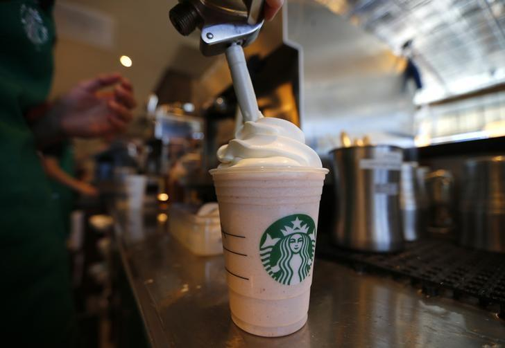 A barista puts whipped cream on a drink at a newly designed Starbucks coffee shop in Fountain Valley, California August 22, 2013.  REUTERS/Mike Blake/ Files