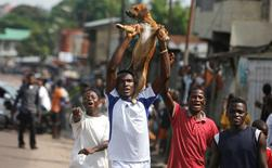 Congolese opposition party supporters carry a dog as they chant slogans in a street of Democratic Republic of Congo's capital Kinshasa, December 19, 2016. REUTERS/Thomas Mukoya