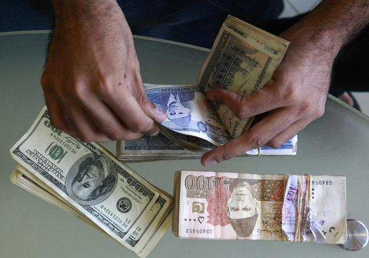 A currency dealer counts Pakistani rupees and U.S. dollars at his shop in Karachi October 8, 2008. REUTERS/Athar Hussain