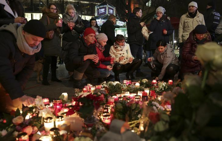 Candles burn at a Christmas market at Breitscheidplatz in Berlin, Germany, December 20, 2016, to commemorate the 12 victims of a truck that ploughed into the crowded market.        REUTERS/Christian Mang
