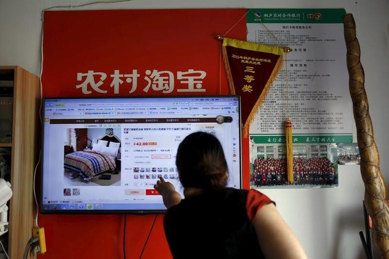 A customer points at a screen displaying a website of Alibaba's Taobao at a rural service centre in Yuzhao Village, Tonglu, Zhejiang province, China, July 20, 2015.REUTERS/Aly Song