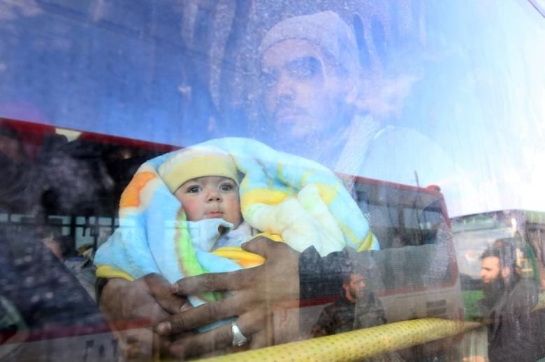 A man with a baby rides a bus to be evacuated from a rebel-held sector of eastern Aleppo, Syria December 18, 2016. REUTERS/Abdalrhman Ismail