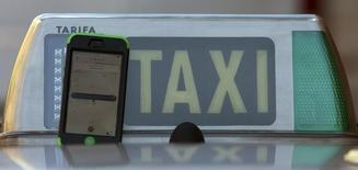 The car-sharing service app Uber on a smartphone next to a taxi sign is seen in this photo illustration taken in Madrid on December 10, 2014. REUTERS/Sergio Perez