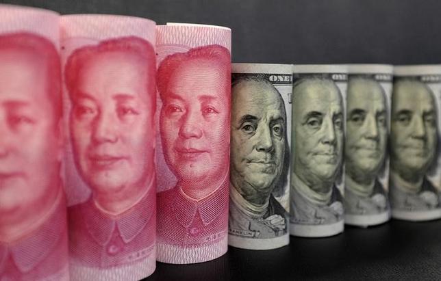 12月22日、中国国家外為管理局(SAFE)の報道官は会見で、中国は米債投資を調整する可能性があり、米債保有の減少は戦術的な動きだと述べた。写真は人民元と米ドルの紙幣、1月撮影(2016年 ロイター/Jason Lee)