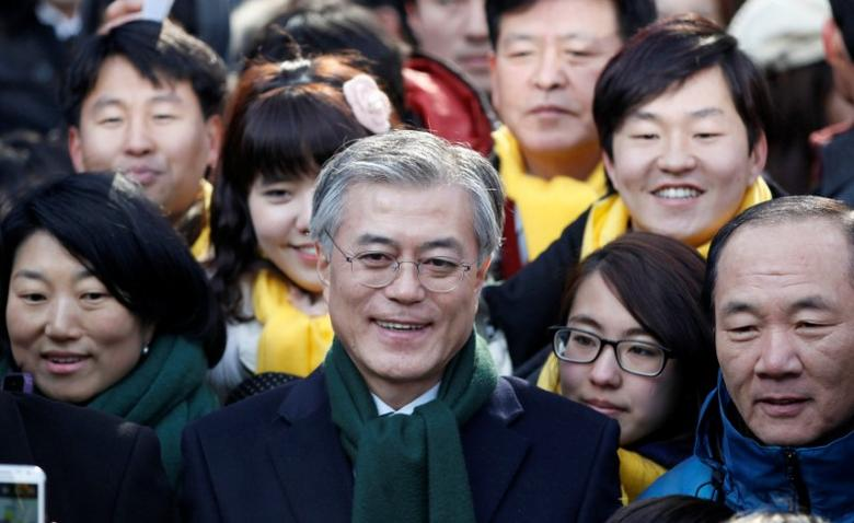 Moon Jae-in (C), former human rights lawyer and presidential candidate of the main opposition Democratic United Party, attends a campaign encouraging people to vote, in Seoul, South Korea December 19, 2012. REUTERS/Kim Hong-Ji/File Photo
