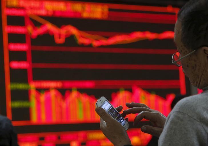 2016年1月5日,中国北京,一家券商营业部内股民用手机查看股票信息。REUTERS/Kim Kyung-Hoon