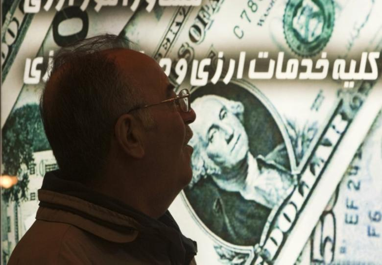 An Iranian man walks past a currency exchange shop in northern Tehran January 3, 2012. The Iranian rial fell to a record low against the dollar on Tuesday following U.S. President Barack Obama signing a bill on  imposing fresh sanctions against the country's central bank.   REUTERS/Morteza Nikoubazl