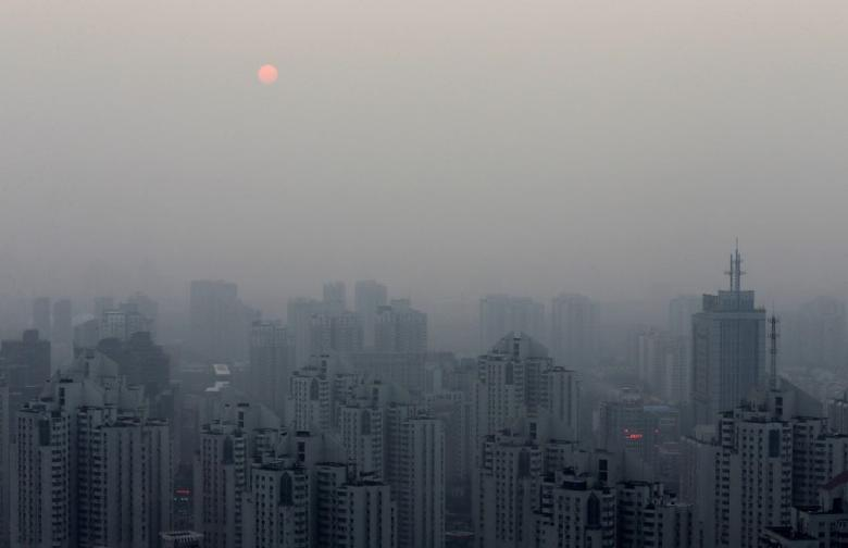 The sun sets above residential buildings on a hazy day in Beijing, September 20, 2014.  REUTERS/Barry Huang/File Photo