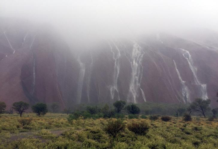 Waterfalls caused by heavy rain run down the side of Australia's famous Uluru rock formation in central Australia, December 26, 2016.   Parks Australia/Handout via REUTERS