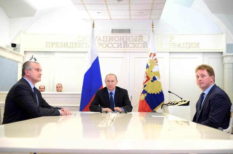 Russian President Vladimir Putin (C), head of Crimea Sergei Aksyonov (L) and Sevastopol Acting Governor Dmitry Ovsyannikov take part in a video link, dedicated to the start of natural gas supplying from mainland Russia to Crimea, in Moscow, Russia, December 27, 2016. Sputnik/Alexei Druzhinin/Kremlin via REUTERS