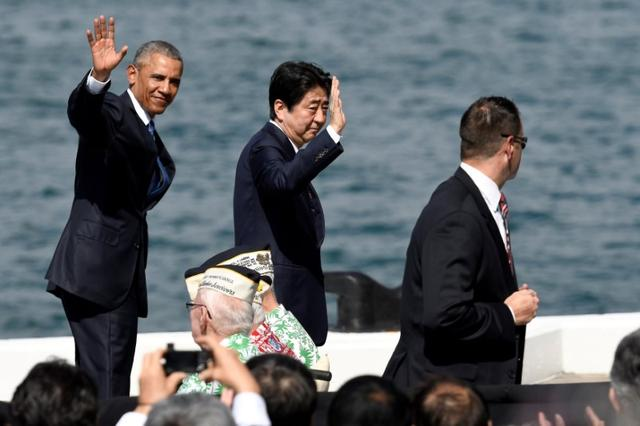 U.S. President Barack Obama and Japanese Prime Minister Shinzo Abe wave to the crowd as they leave after giving remarks at Kilo Pier overlooking the USS Arizona Memorial at Joint Base Pearl Harbor-Hickam in Honolulu, Hawaii, U.S. December 27, 2016. REUTERS/Hugh Gentry
