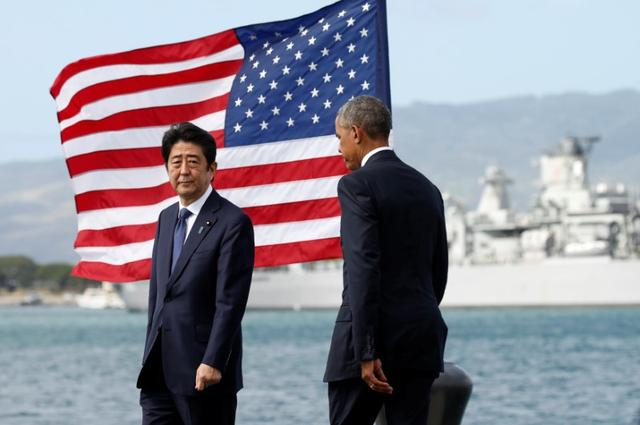 Japanese Prime Minister Shinzo Abe and U.S. President Barack Obama take the stage to deliver remarks at Joint Base Pearl Harbor-Hickam, Hawaii, U.S., December 27, 2016. Pictured in the background is the USS Missouri. REUTERS/Kevin Lamarque