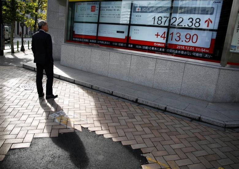 A man looks at an electronic board showing Japan's Nikkei average outside a brokerage in Tokyo, Japan, December 1, 2016. REUTERS/Kim Kyung-Hoon