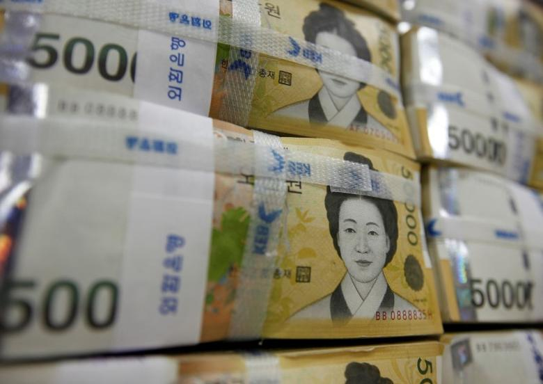 Fifty thousand won notes are piled up after being counted at a bank during a photo opportunity in Seoul October 13, 2010.   REUTERS/Lee Jae-Won/File Photo