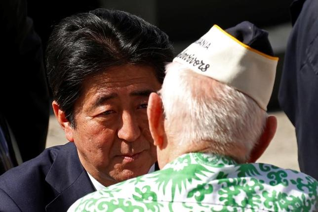 Japanese Prime Minister Shinzo Abe speaks with a Pearl Harbor survivor after he and U.S. President Barack Obama spoke at Joint Base Pearl Harbor-Hickam, Hawaii, U.S., December 27, 2016.. REUTERS/Kevin Lamarque