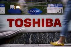 Imagen de archivo, peatones caminan frente al logo de Toshiba fuera de una tienda electrónica en Tokio, Japón. 25 de junio 2015.Las acciones de Toshiba caían más de un 19 por ciento en las operaciones de la mañana del jueves, en su tercer día de fuertes pérdidas después de que el conglomerado tecnológico nuclear japonés dijo esta semana que enfrenta una potencial amortización por miles de millones de dólares. REUTERS/Yuya Shino/File Photo