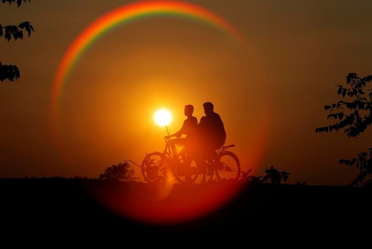 Boys are silhouetted against the setting sun as they ride bicycles on the outskirts of Agartala, India, November 21, 2016. REUTERS/Jayanta Dey/Files