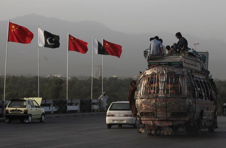 People sit on top of a bus as they go past flags of Pakistan and China that are displayed along a road, ahead of Chinese Premier Li Keqiang's visit to Islamabad May 21, 2013. REUTERS/Faisal Mahmood