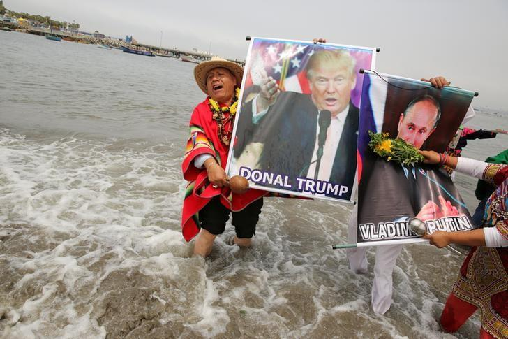 Peruvian shamans holding a poster of U.S. President-elect Donald Trump and Russian President Vladimir Putin perform a ritual of predictions for the new year at Pescadores beach in Chorrillos, Lima, Peru, December 29, 2016. REUTERS/Mariana Bazo