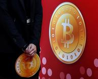 Atendente segura logo do Bitcoin durante inauguração de loja da empresa em Hong Kong. 28/02/2014 REUTERS/Bobby Yip