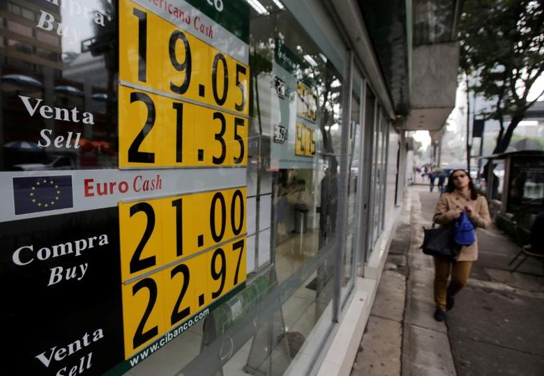 A woman walks past a board displaying the exchange rate for Mexican peso against the U.S. dollar and the Euro at a bank in Mexico City, Mexico, November 17, 2016. REUTERS/Henry Romero
