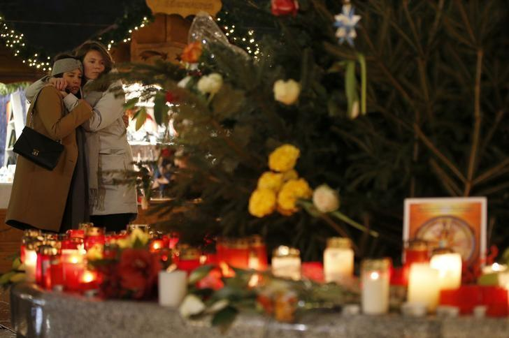 People mourn beside flowers and candles placed at the Christmas market at Breitscheid square in Berlin, Germany, December 22, 2016, following an attack by a truck which ploughed through a crowd at the market on Monday night.      REUTERS/Fabrizio Bensch