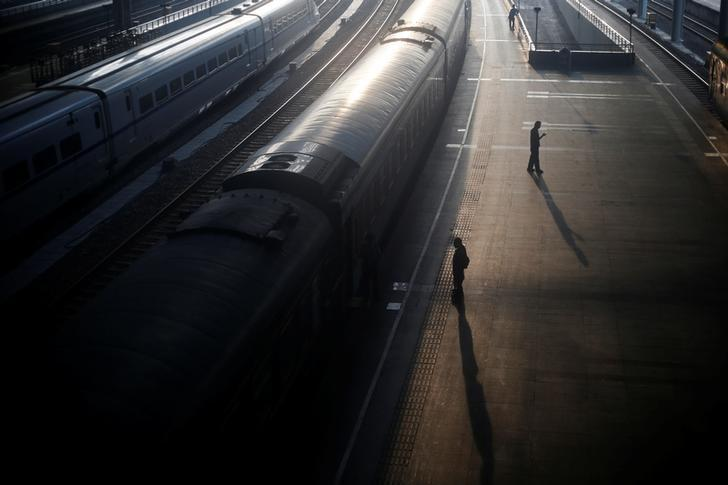 People stand next to a train at a railway station in Nanjing, Jiangsu Province, China June 6, 2016. REUTERS/Aly Song