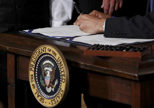 FILE PHOTO - U.S. President Barack Obama signs the Affordable Care Act, dubbed Obamacare, the comprehensive healthcare reform legislation during a ceremony in the East Room of the White House in Washington, U.S., March 23, 2010. REUTERS/Jim Young/File Photo