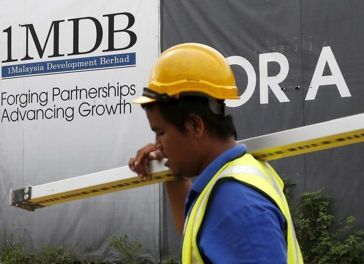 A construction worker walks past a 1Malaysia Development Berhad (1MDB) billboard at the Tun Razak Exchange development in Kuala Lumpur, Malaysia February 3, 2016. REUTERS/Olivia Harris/File Photo