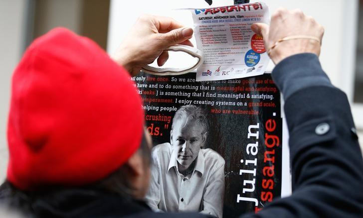 A supporter of Julian Assange holds a poster after prosecutor Ingrid Isgren from Sweden arrived at Ecuador's embassy to interview him in London, Britain, November 14, 2016.  REUTERS/Peter Nicholls/Files