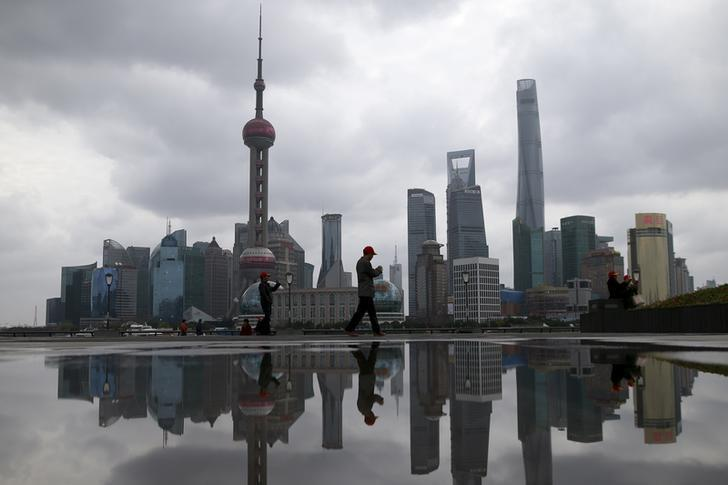 People walk on the bund in front of the financial district of Pudong in Shanghai, China March 9, 2016. REUTERS/Aly Song