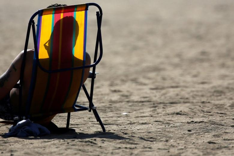 A man lays out in the sun during warm weather at Orchard Beach in the Bronx borough of New York, U.S., October 19, 2016. REUTERS/Shannon Stapleton