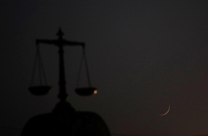 The crescent moon is seen above the Distrct High Court as Muslims attend an evening mass prayer session called ''tarawih'' to mark the holy fasting month of Ramadan at a mosque in Karachi, Pakistan, June 6, 2016. REUTERS/Akhtar Soomro/Files