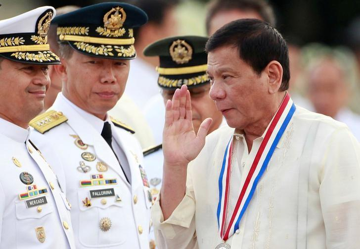 President Rodrigo Duterte returns the salute of a military officer (not pictured) as he leads the death anniversary celebration of Filipino national hero Dr Jose Rizal in Manila, Philippines December 30, 2016.  REUTERS/Czar Dancel/Files