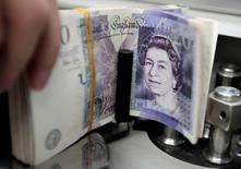 La livre sterling faiblira encore un peu contre l'euro et le dollar une fois le processus de sortie de la Grande-Bretagne de l'Union européenne (Brexit) officiellement lancé, montre une enquête de Reuters publiée vendredi qui souligne aussi la prédominance des risques baissiers. /Photo d'archives/REUTERS/Sukree Sukplang