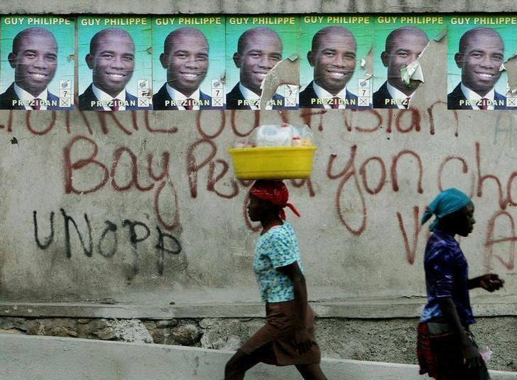 Haitians walk past posters of Guy Philippe at a street in Port-au-Prince, Haiti, February 3, 2006. REUTERS/Eduardo Munoz