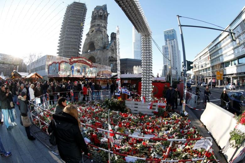 Flowers and candles are placed at the Christmas market at Breitscheid square in Berlin, Germany, December 30, 2016, following an attack by a truck which ploughed through a crowd at the market.   REUTERS/Fabrizio Bensch