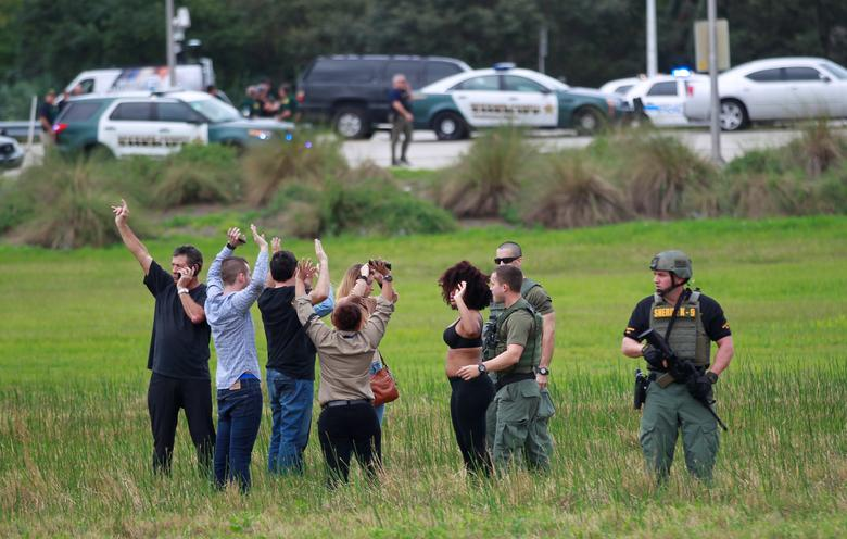 Law enforcement officers move in to verify the identity of people in this field just outside the airport perimeter following a shooting incident at Fort Lauderdale-Hollywood International Airport in Fort Lauderdale, Florida, U.S. January 6, 2017. REUTERS/Andrew Innerarity/Files