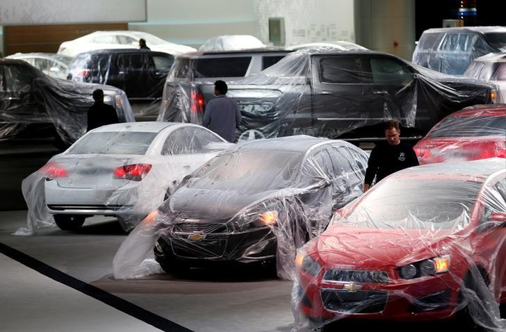 Vehicles are covered with protective wrap as workers prepare the General Motors automakers display ahead of the media preview of the North American International Auto Show at Cobo Center in Detroit, Michigan January 11, 2014. REUTERS/Rebecca Cook/Files