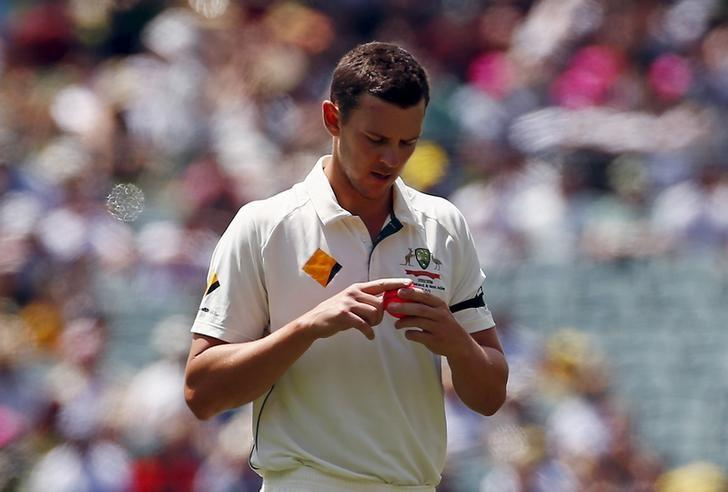 Australia's Josh Hazlewood shines the pink ball as he prepares to bowl during the first day of the third cricket test match against New Zealand at the Adelaide Oval, in South Australia, November 27, 2015.    REUTERS/David Gray/Files