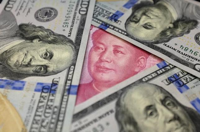 1月7日、中国人民銀行(中央銀行)が発表した12月末時点の中国外貨準備高は3兆0110億ドルで、何とか3兆ドルを死守したものの、2011年2月以来の低水準まで減少した。写真は人民元とドルの紙幣、昨年1月撮影(2017年 ロイター/Jason Lee)