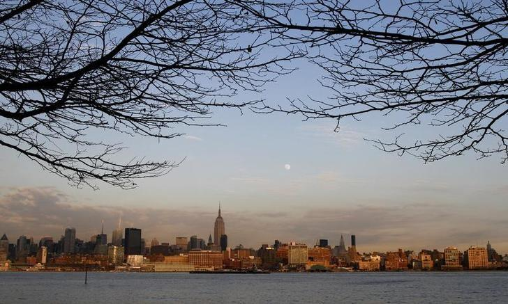 The moon rises behind the  Empire State Building and the skyline of Manhattan at sunset in New York, February 16, 2011. REUTERS/Gary Hershorn
