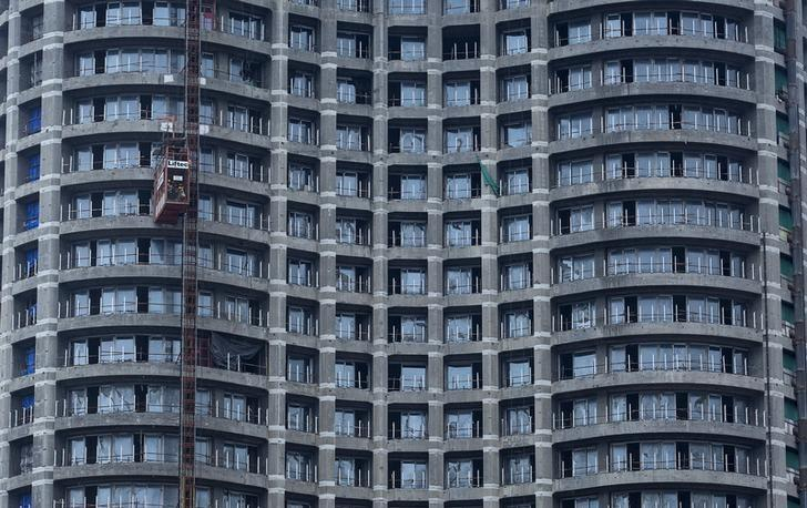 Workers take a lift at an under construction high-rise residential tower in Mumbai's central financial district August 25, 2014. REUTERS/Danish Siddiqui/Files