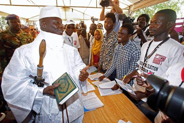 Gambian President Yahya Jammeh holds a copy of the Quran while speaking to a poll worker at a polling station during the presidential election in Banjul, Gambia, December 1, 2016. REUTERS/Thierry Gouegnon
