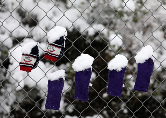 Socks that belong to stranded refugee children are covered by snow as they hang on a fence during a snowstorm at a refugee camp north of Athens, Greece January 10, 2017.REUTERS/Yannis Behrakis