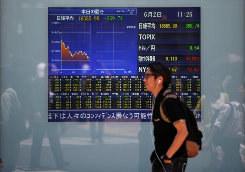 A man walks in front of a screen showing today's movements of Nikkei share average outside a brokerage in Tokyo, Japan, June 2, 2016.  REUTERS/Issei Kato