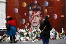 معجبون يضعون الزهور أمام جدارية مرسوم عليها وجه ديفيد بوي في جنوب لندن في الذكري الأولى لوفاته يوم الثلاثاء. تصوير: ستيفان ورموث - رويترز