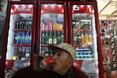 Un hombre bebe un refresco en una tienda en México.9 de septiembre de 2013. La mexicana Arca Continental, la segunda mayor embotelladora de Coca-Cola en América Latina, dijo el miércoles que este año invertirá 4,000 millones de pesos (183.1 millones de dólares) en sus operaciones en México, un aumento de un 25 por ciento frente a los 3,200 millones de pesos de 2016. REUTERS/Edgard Garrido